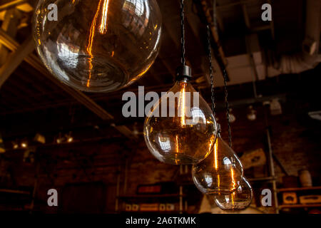 vintage large hanging glass lightbulbs with orange glow - Stock Photo