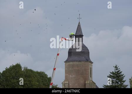 Repairs to the slate roof of an 18th century church steeple using a an aerial work platform, or spider lift - Stock Photo