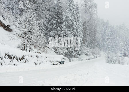 Snowy road among pine trees in winter with an SUV parked. - Stock Photo