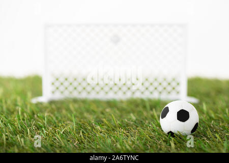 selective focus of toy soccer ball and football gates on green field isolated on white, sports betting concept - Stock Photo