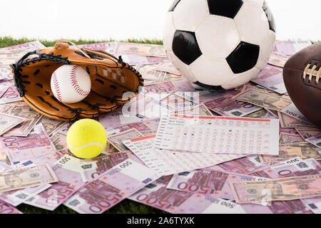 baseball glove and ball, soccer, tennis and rugby balls near betting lists on euro and dollar banknotes isolated on white, sports betting concept - Stock Photo