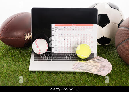 laptop near sports balls and betting list on green grass isolated on white, sports betting concept - Stock Photo