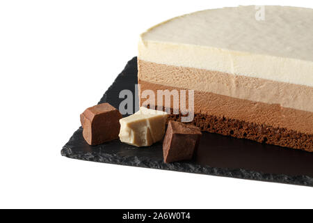 Delicious cake with three different kind of chocolate on plate of shale. Isolated on white background. - Stock Photo