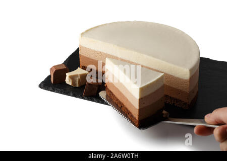 Delicious cake with three different kind of chocolate on plate of shale. Isolated on white background.  Cook picks up a cut piece of cake on a pastry - Stock Photo