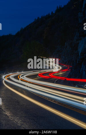 Hawks Nest Light Show - Car trails along the winding route 97 during the autumn foliage season in Sparrow Bush, New York. - Stock Photo