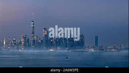 Icons of New York City - Fog rolls in this panoramic view of the illuminated midtown Manhattan skyline with the Empire State Building (ESB) lit up in - Stock Photo