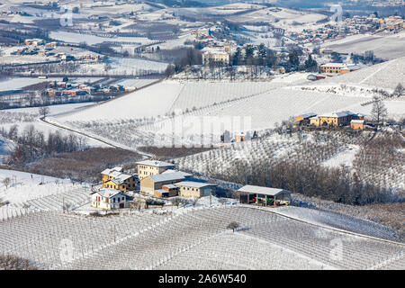 View from above an hamlets and villages among vineyards on the hills covered in snow in Piedmont, Northern Italy.