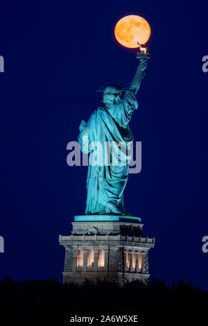 The super moon rises over the Statue of Liberty during the blue hour The full moon lines up perfect with the statues torch. - Stock Photo