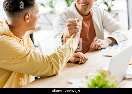 cropped view of two young businessmen shaking hands while sitting together at workplace - Stock Photo