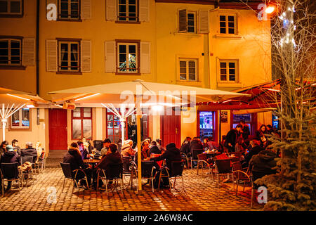 Strasbourg, France - Dec 27, 2017: Busy evening at the outdoor bar restaurant terraces in Place du Marche Gayot square during winter holidays - Stock Photo