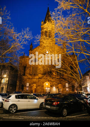 Strasbourg, France - Dec 27, 2017: Majestic building of Eglise protestante du Temple Neuf with cars parked in front on the large square - Stock Photo