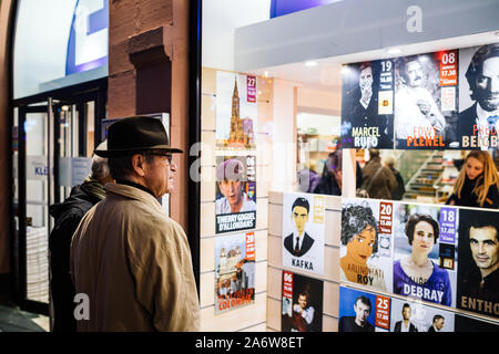Strasbourg, France - Dec 27, 2017: Side view of beautiful adult man wearing classic hat reading diverse bookstore announcement with writers arriving to sing books - Stock Photo