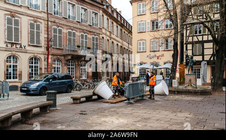 Strasbourg, France - Dec 27, 2017: Workers arranging christmas decorations large white illuminated vases in French city center near Piano Grill bar cafe - Stock Photo
