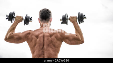 Muscular man exercising with dumbbell rear view. Pain is temporary, pride is forever. Sportsman with strong back and arms. Sport equipment. Bodybuilding sport. Sport lifestyle. Dumbbell exercise gym. - Stock Photo