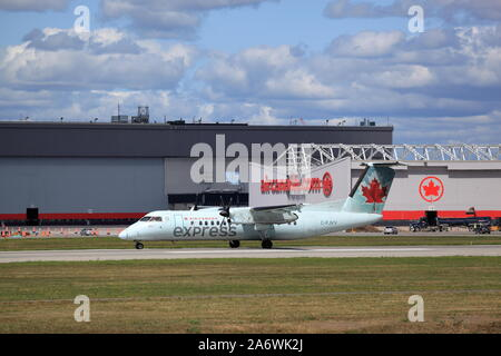 De Havilland Dash 8 C-FJVV Air Canada Express taxiing by Air Canada hangar at Montreal International Airport, Quebec, Canada, August 23, 2019 - Stock Photo