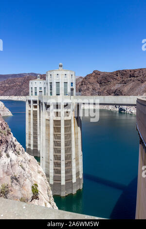 Penstock towers of the Hoover Dam with blue sky and blue waters of Lake Mead behind it - Stock Photo