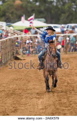 Woman on horseback galloping in the arena waving her hand at spectators during the start of the 54th annual Makawao Rodeo, Oskie Rice Arena, Makawao, - Stock Photo
