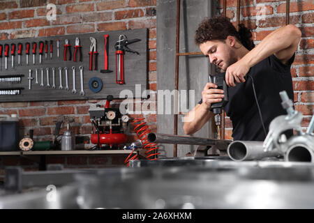 man in home workshop garage work drilling metal with drill, repair iron pipe on the workbench full of wrenches, diy and craft concept - Stock Photo