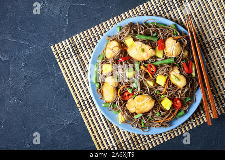 Chicken and Mango Soba Noodle Salad with steamed green beans, shredded carrots, chili peppers and spring onions on a plate on a concrete table  with c - Stock Photo
