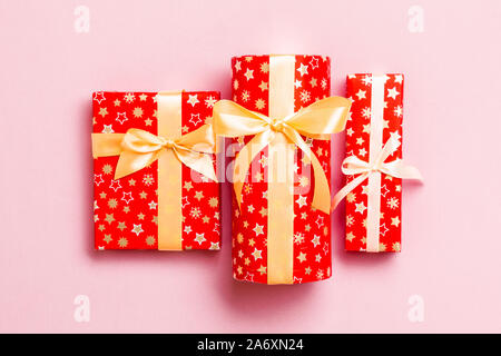 Gift box with gold bow in hands for Christmas or New Year day on pink background, top view. - Stock Photo