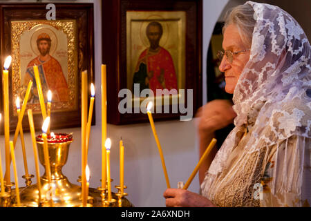 An elderly woman puts a candle near the iconostasis in the Temple of the Holy prophet of God Elijah, in Kitay-Gorod, on Elijah's day - Stock Photo