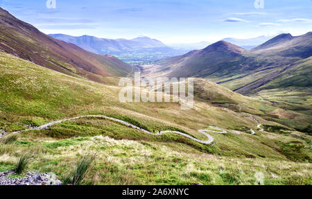 Three distant hikers walking up a winding rocky path from Coledale Beck that leads to Hopegill Head, Crag Hill and Grasmoor in the Lake District. - Stock Photo