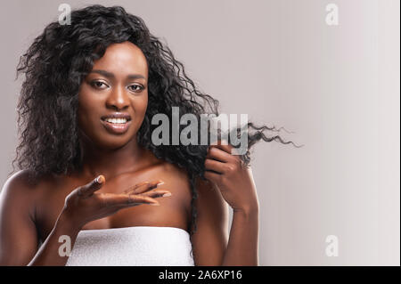 Upset black woman pointing at split ends of her hair - Stock Photo