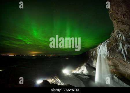 Aurora Borealis, The Northern Lights, break through the clouds at Seljalandsfoss waterfall in Southern Iceland as it begins to freeze. - Stock Photo