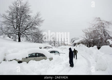 Unrecognizable man cleaning the snow in front of a car, covered in snow. People and vehicle concept. Cleaning snow, snowfall during winter season - Stock Photo