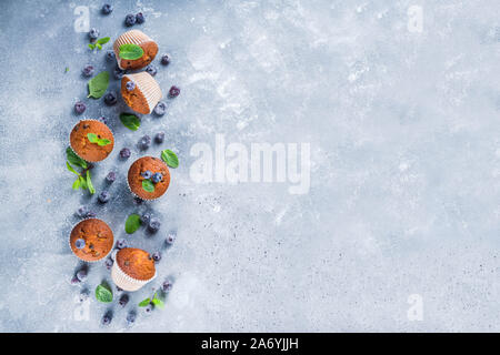 Blueberry muffins with fresh berries and mint, grey stone or concrete background top view - Stock Photo