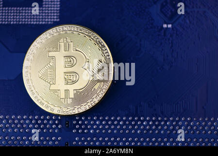Golden Cryptocurrency coins on computer circuit board - image - Stock Photo