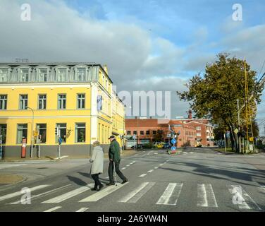 An elderly couple on a pedestrian crossing in front of a bright yellow hotel in Ystad, Sweden. - Stock Photo