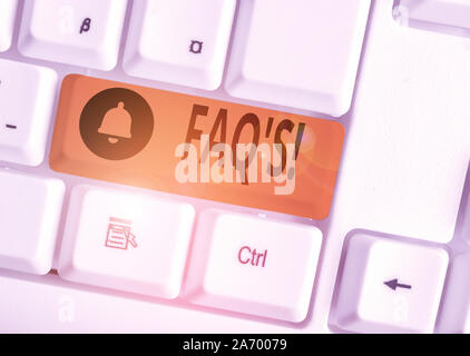 Text sign showing Faq S. Business photo text list of questions and answers relating to particular subject White pc keyboard with empty note paper abov - Stock Photo