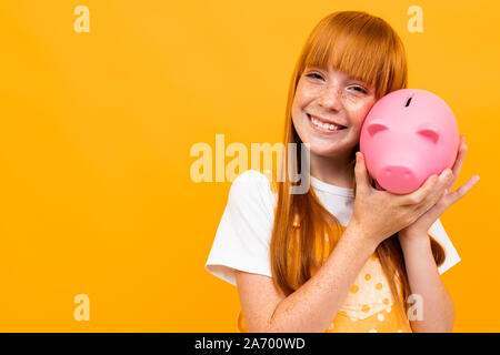 schoolgirl on an orange background hugs a piggy bank in the form of a pink pig - Stock Photo