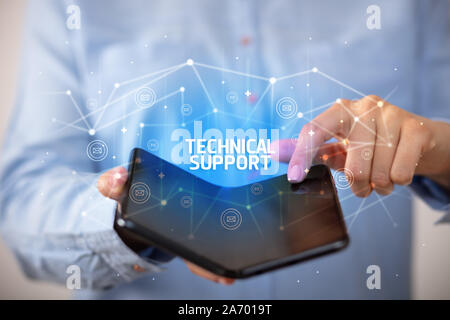 Businessman holding a foldable smartphone with TECHNICAL SUPPORT inscription, new technology concept