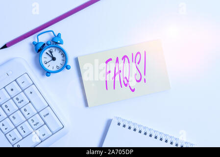 Text sign showing Faq S. Business photo text list of questions and answers relating to particular subject White pc keyboard with empty note paper and - Stock Photo