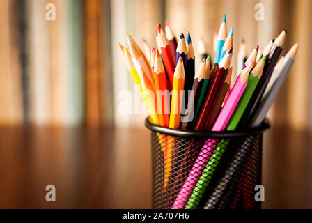 Wire desk tidy full of coloured pencils standing on a wooden table in front of a bookshelf full of books with shallow dof and copyspace - Stock Photo