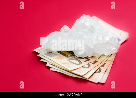 Lot of 50 euro bank notes under white pure crystal gemstone on red background. Conceptual image of business and finances in semi precious gemstone. - Stock Photo