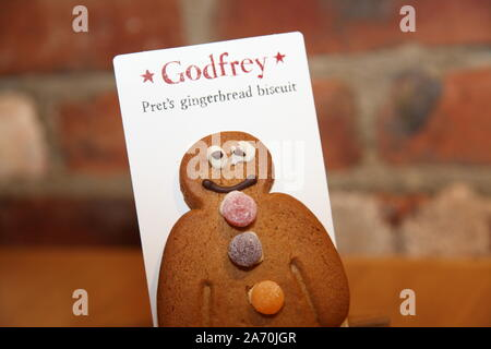 Godfrey, Pret's gingerbread man biscuit with a badly iced eye against brick background - Stock Photo