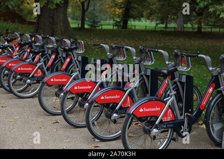 Santander sponsored city bikes for rent in London. AKA Boris bikes, hire bicycles lined up in Hyde Park, London - Stock Photo