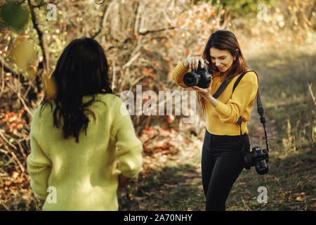 young woman photographer takes pictures of model in nature, the photographer in action - Stock Photo