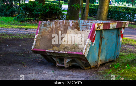 large container filled with sand, construction and transport equipment - Stock Photo