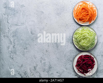 Vegetable noodles - zucchini, carrot, and beetroot noodles on plate over gray cement background. Clean eating, raw vegetarian, food concept. Copy space for text. Top view or flat lay. - Stock Photo