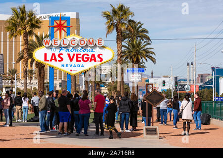 A crowd of tourists stand in line for photos at the Welcome to Fabulous Las Vegas sign in Las Vegas, Nevada, USA. - Stock Photo