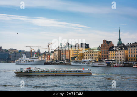 Stockholm waterfront, view in summer of the Old Town (Gamla Stan) waterfront with a tourist cruise boat in the foreground, central Stockholm, Sweden. - Stock Photo