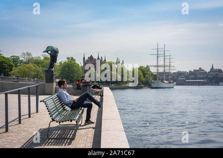 Stockholm waterfront, view in summer of a young man relaxing on a bench along the Blasieholmen waterfront in central Stockholm, Sweden. - Stock Photo