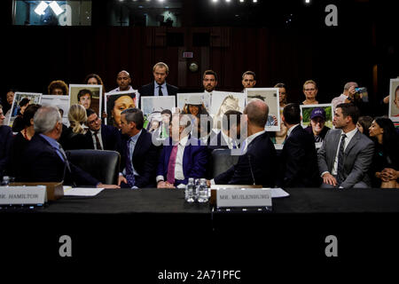 (191029) -- WASHINGTON, Oct. 29, 2019 (Xinhua) -- Boeing CEO Dennis Muilenburg (1st R, front) looks back at the family members of 737 Max crash victims as he attends a hearing before U.S. Senate Committee on Commerce, Science and Transportation on Capitol Hill in Washington, DC, the United States, on Oct. 29, 2019. Boeing CEO Dennis Muilenburg acknowledged mistakes as he testified before the U.S. Congress for the first time since two deadly air crashes of its 737 Max planes that killed 346 people, but he deflected tough questions such as why the company withheld details about its flawed new a - Stock Photo