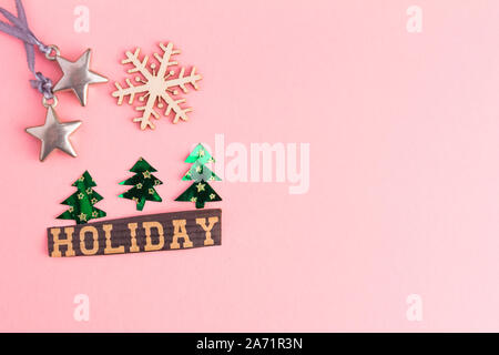Christmas trees, toy stars, snowflake and Holiday lettering inscription on a pink background. Winter Holiday festive greeting gift card with copy - Stock Photo