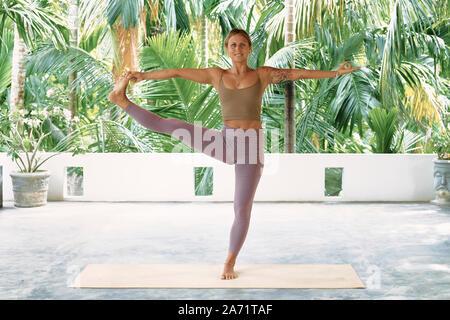 woman practicing advanced yoga on organic mat series of