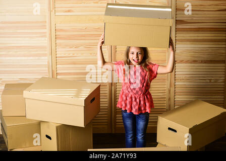 happy little girl sit in room on boxes. purchase of new habitation. happy child cardboard box. repair of room. new apartment. unpacking moving boxes. Cardboard boxes - moving to a new house. - Stock Photo